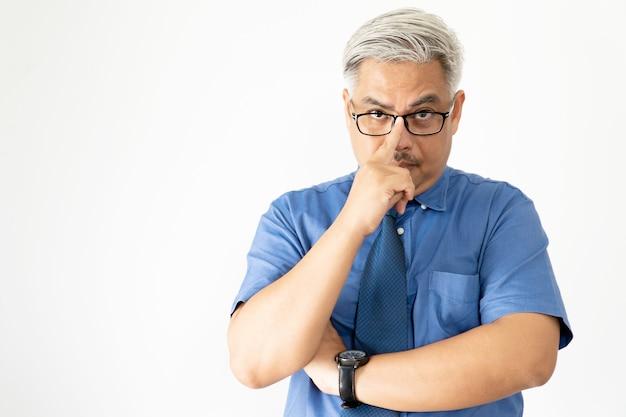 Portret zekere aziatische bedrijfsmens die glazen en het overhemd van de korte mouw dragen die aan camera op wit kijken