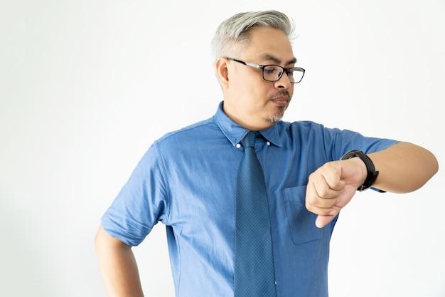 Portret zekere aziatische bedrijfsmens die glazen en het overhemd van de korte mouw dragen polshorloge op wit bekijken