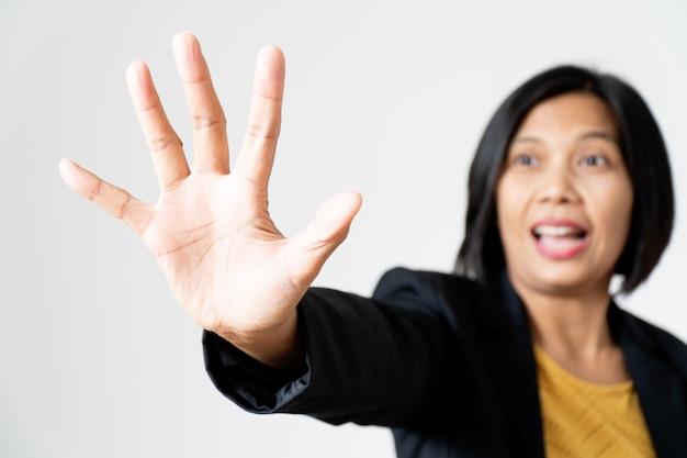 Portret zekere aziatische bedrijfsvrouw die handeinde met opwindend gezicht op wit voorstellen