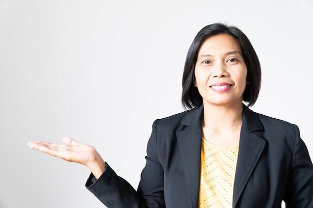 Portret zekere aziatische bedrijfsvrouw die met hand op wit voorstellen