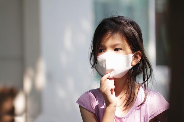 Portretbeeld van aziatisch basisschoolmeisje dat masker draagt voor preventie van coronavirus