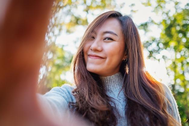 Portretbeeld van een gelukkige mooie aziatische vrouw die selfie foto in park maakt