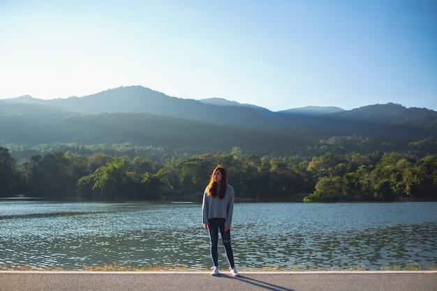 Portretbeeld van een mooie aziatische vrouw die alleen staat voor het meer en de bergen op een zonnige dag