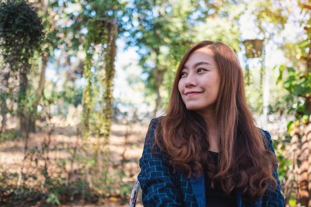 Portretbeeld van een mooie aziatische vrouw die in de buitenlucht zit