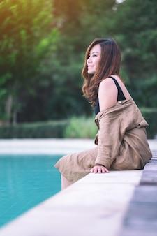 Portretbeeld van een mooie aziatische vrouw genoot van het zitten bij het zwembad
