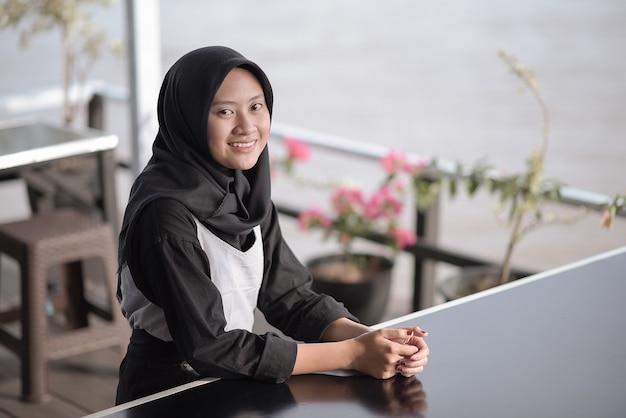 Portretbeeld van een mooie jonge moslimvrouw die in café zit en glimlacht