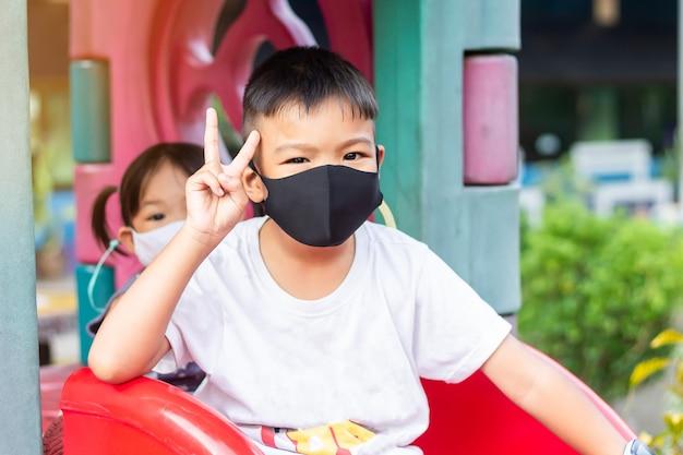 Portretbeeld van jonge aziatische kindbroer die medische maskerbescherming voor zijn kleine babyzusje draagt.