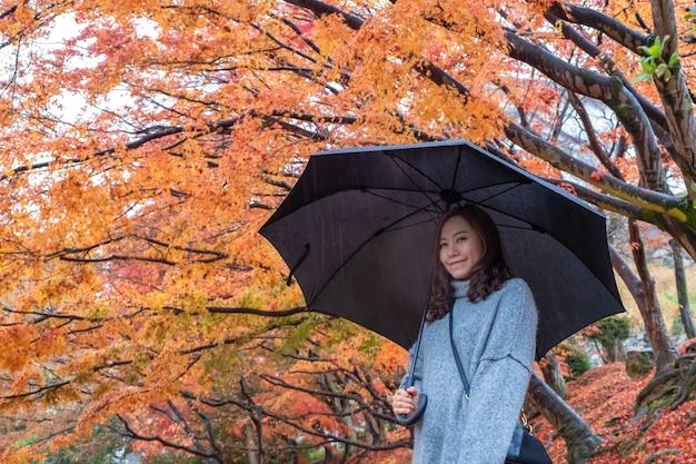 Portretbeeld van mooie aziatische vrouw die zich in de regen met rode en oranje boombladeren op de herfstachtergrond bevindt