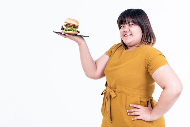 Portretbeelden van aziatische aantrekkelijke dikke vrouw, zijn blij, glimlachen en houden hamburger vast