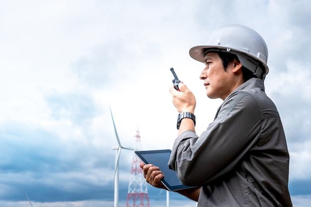 Portretbeelden van een aziatische man van de ingenieurstechnicus die een tablet vasthoudt en radiocommunicatie gebruikt met onscherpte van windturbines, wolken en hemelachtergrond