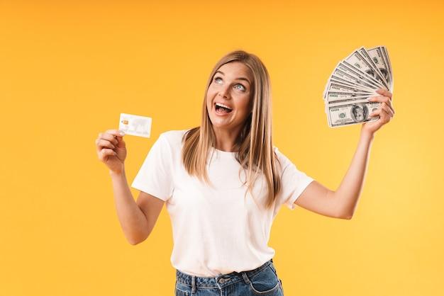 Portretclose-up van blonde vrouw die casual t-shirt draagt dat zich verheugt terwijl ze creditcard en contant geld vasthoudt over gele muur