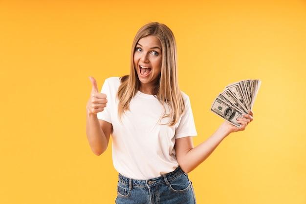 Portretclose-up van een blonde vrouw die een casual t-shirt draagt met duim omhoog terwijl ze contant geld vasthoudt dat over een gele muur wordt geïsoleerd
