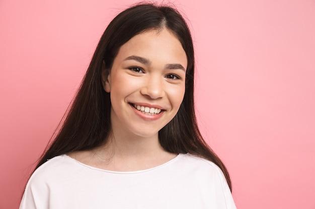 Portretclose-up van een jong gelukkig meisje met lang donker haar dat naar voren kijkt en lacht, geïsoleerd over roze muur