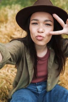 Portretclose-up van een verleidelijke vrouw met lang donker haar met een hoed die lacht en een vredesteken toont terwijl ze selfie maakt