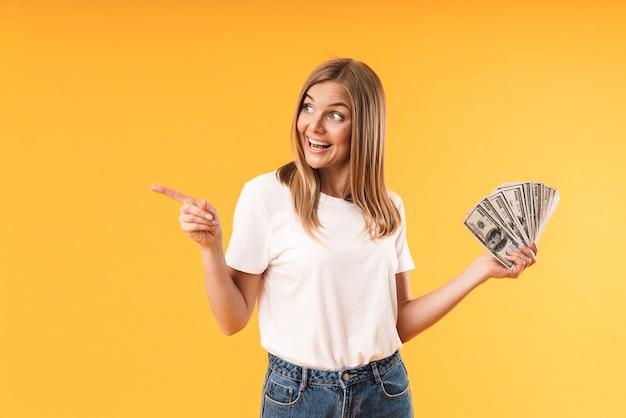 Portretclose-up van een vrolijke blonde vrouw die een casual t-shirt draagt dat met de vinger wijst naar copyspace terwijl ze contant geld vasthoudt dat over een gele muur wordt geïsoleerd