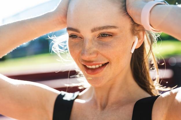 Portretclose-up van een vrolijke sportvrouw die een trainingspak en oordoppen draagt en haar haar aanraakt tijdens de training in het stadspark