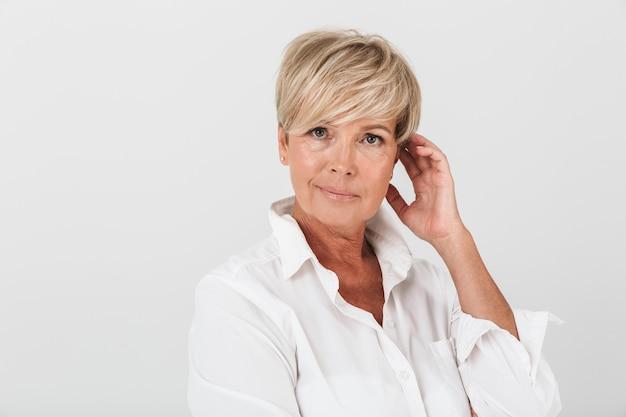 Portretclose-up van elegante volwassen vrouw met kort blond haar die camera bekijkt die over witte muur in studio wordt geïsoleerd