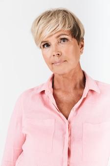 Portretclose-up van ernstige vrouw van middelbare leeftijd met kort blond haar die camera bekijkt die over witte muur in studio wordt geïsoleerd
