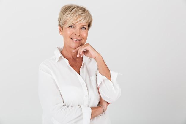 Portretclose-up van gelukkige volwassen vrouw met kort blond haar die bij camera glimlacht die over witte muur in studio wordt geïsoleerd