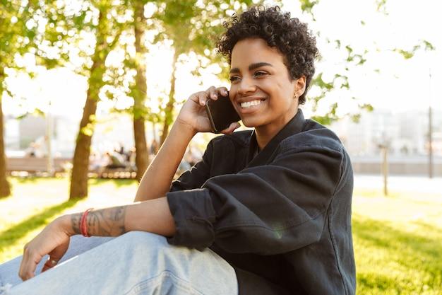 Portretclose-up van gelukkige vrouw met krullend haar die op smartphone spreekt terwijl het zitten op bank in stadspark