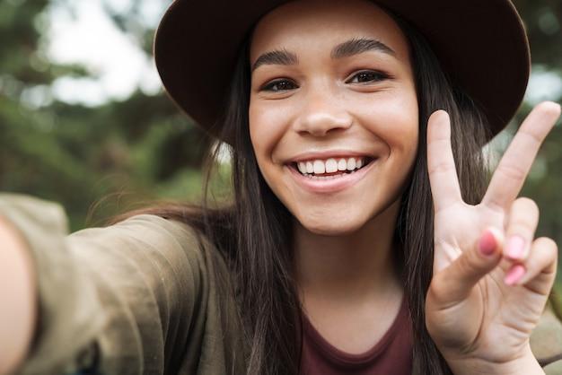 Portretclose-up van gelukkige vrouw met lang donker haar die hoed draagt die glimlacht en vredesteken toont terwijl het nemen van selfie