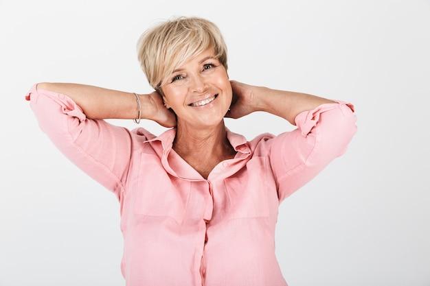 Portretclose-up van gelukkige vrouw van middelbare leeftijd met kort blond haar die bij camera glimlacht die over witte muur in studio wordt geïsoleerd