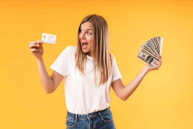 Portretclose-up van jonge blonde vrouw die een toevallig t-shirt draagt dat zich verheugt terwijl ze creditcard en contant geld vasthoudt, geïsoleerd over gele muur