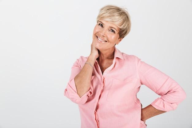 Portretclose-up van kaukasische vrouw van middelbare leeftijd met kort blond haar die bij camera glimlacht die over witte muur in studio wordt geïsoleerd