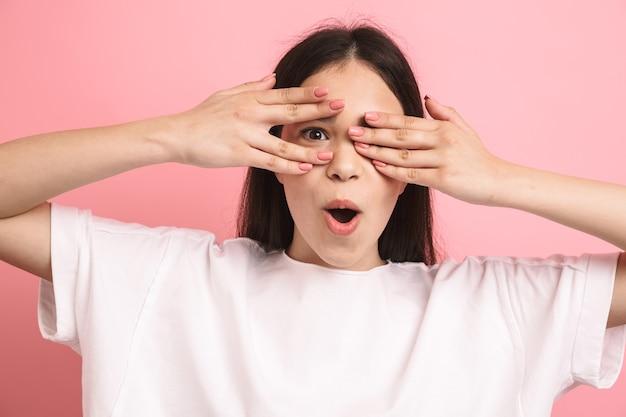 Portretclose-up van lief positief meisje met lang donker haar dat haar ogen bedekt en door handen gluurt die over roze muur worden geïsoleerd