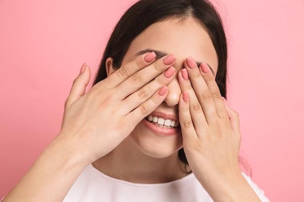 Portretclose-up van lief, vrolijk meisje met lang donker haar dat haar ogen bedekt en gluurt door handen geïsoleerd over roze muur