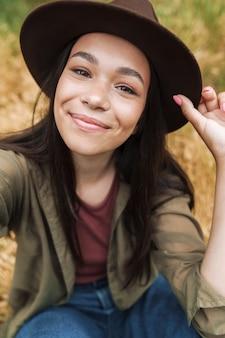 Portretclose-up van mooie vrouw met lang donker haar die hoed draagt die bij camera glimlacht terwijl het nemen van selfie