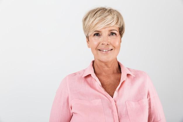 Portretclose-up van mooie vrouw van middelbare leeftijd met kort blond haar die bij camera glimlacht die over witte muur in studio wordt geïsoleerd