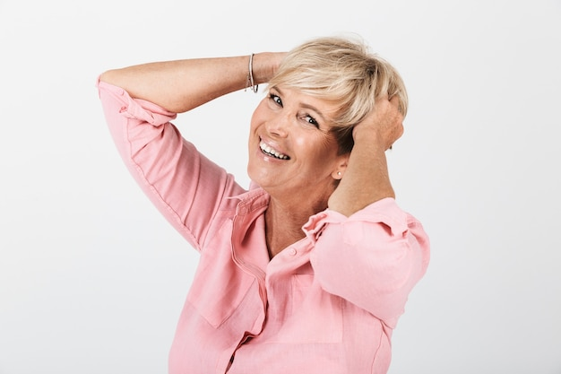Portretclose-up van opgewekte vrouw van middelbare leeftijd met kort blond haar die bij camera glimlacht die over witte muur in studio wordt geïsoleerd
