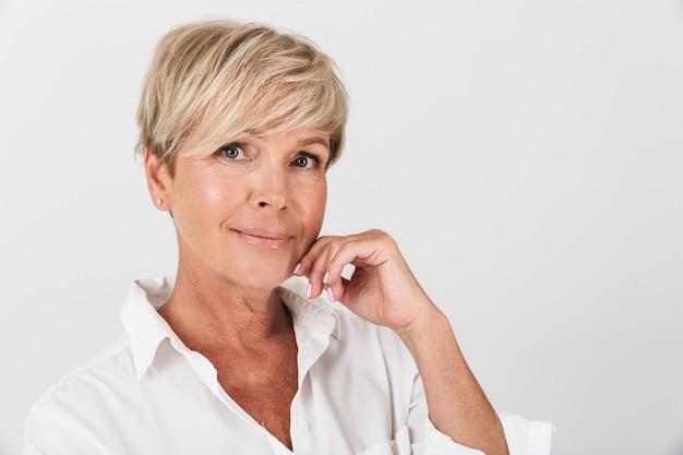 Portretclose-up van optimistische volwassen vrouw met kort blond haar die camera bekijkt die over witte muur in studio wordt geïsoleerd