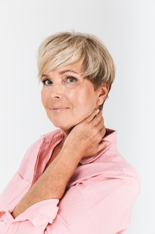 Portretclose-up van optimistische vrouw van middelbare leeftijd met kort blond haar die bij camera glimlacht die over witte muur in studio wordt geïsoleerd