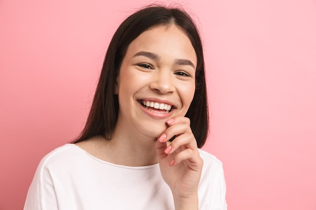 Portretclose-up van positief gelukkig meisje met lang donker haar dat naar voren kijkt en lacht, geïsoleerd over roze muur