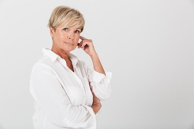 Portretclose-up van schitterende volwassen vrouw met kort blond haar die camera bekijkt die over witte muur in studio wordt geïsoleerd