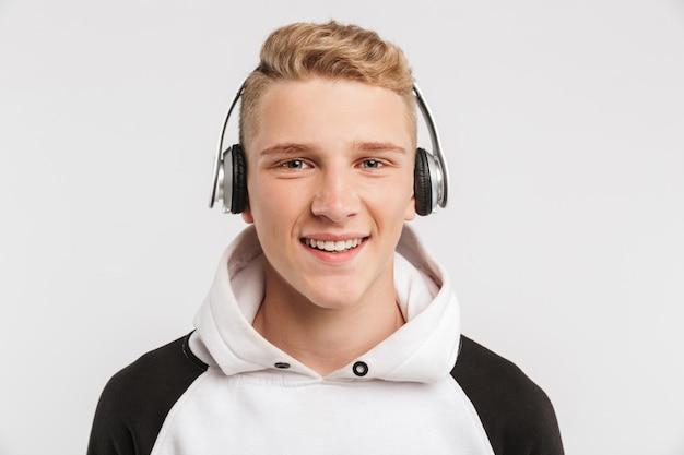 Portretclose-up van tiener 16-18 jaar oud dragend hoodie en draadloze hoofdtelefoons die die met gelukkige glimlach stellen op wit wordt geïsoleerd