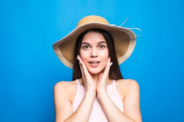 Portretclose-up van verraste vrouw die strohoed met handen op wangen draagt die over blauwe muur wordt geïsoleerd.