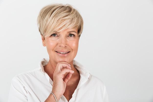 Portretclose-up van vrolijke volwassen vrouw met kort blond haar die bij camera glimlacht die over witte muur in studio wordt geïsoleerd