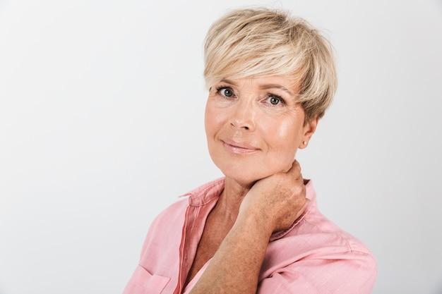 Portretclose-up van vrolijke vrouw van middelbare leeftijd met kort blond haar die bij camera glimlacht die over witte muur in studio wordt geïsoleerd