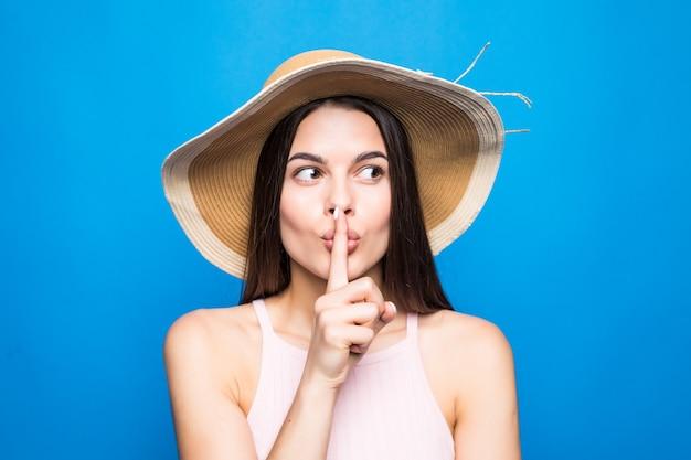 Portretclose-up van vrouw die strohoed draagt die vinger toont aan lippen om geheim over blauwe muur te houden.