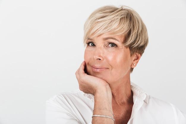 Portretclose-up van vrouw op middelbare leeftijd met kort blond haar die camera bekijkt die over witte muur in studio wordt geïsoleerd
