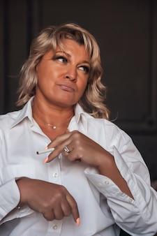 Portretfoto schattige middelbare leeftijd 45 jaar oude blonde vrouw in huiskamer. vrouw in witte kleren in donker interieur. op blote voeten met sigaretten. binnenshuis positieve zelfverzekerde volwassen vrouw. ruimte kopiëren