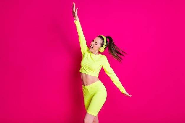 Portretfoto van een actief meisje met een koptelefoon in sportkleding die aan het oefenen is met het luisteren naar muziek geïsoleerd op een levendige fuchsiakleurige achtergrond