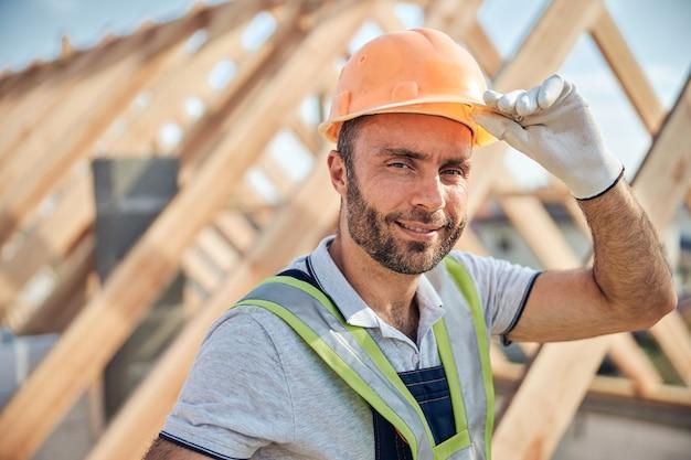 Portretfoto van een ervaren bouwer die zijn helm aanraakt en naar de camera kijkt