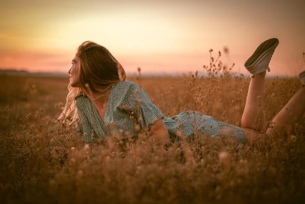 Portretfoto van een gelukkige blanke blonde vrouw in een zomerjurk die tijdens de zonsondergang in een veld ligt