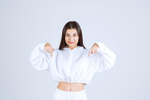 Portretfoto van een jong meisjesmodel dat naar beneden wijst.