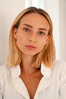 Portretfoto van een jonge vrouw op een witte achtergrond. vrouw in wit overhemd bij het raam