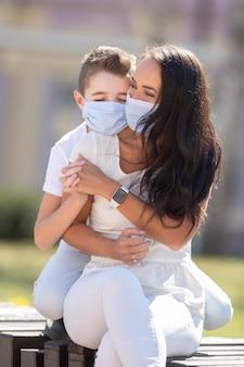 Portretfoto van een jongen die zijn moeder vanaf de achterkant knuffelt, handen vasthoudt terwijl hij buiten is, met gezichtsmaskers op.
